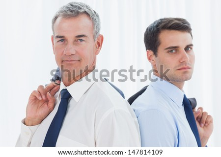 Serious businessmen in bright office posing back to back together while holding their jacket