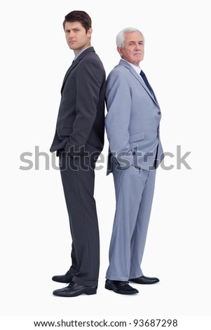 Serious businessmen standing back to back against a white background