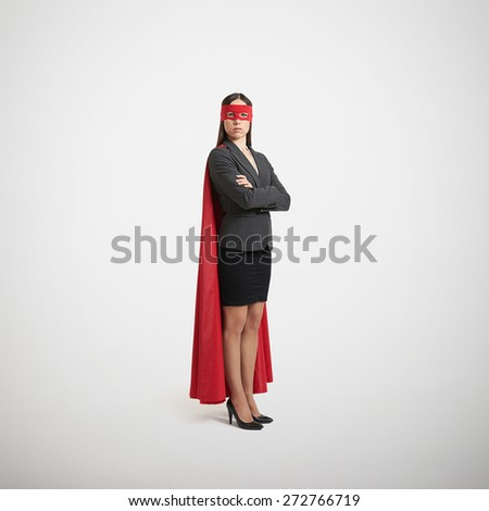 serious businesswoman dressed as a superhero in red mask and cloak over light grey background - stock photo