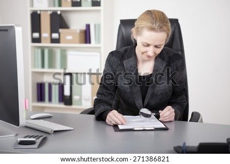 Serious Businesswoman in Black Suit Reading Documents on a Clipping Board Using a Magnifying Glass While Sitting at her Office. - stock photo
