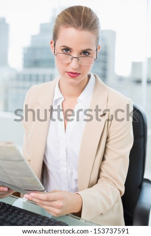 Serious businesswoman in bright office holding newspaper - stock photo
