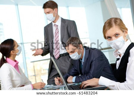 Serious businesswoman in mask working in the office - stock photo
