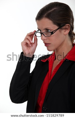 Serious businesswoman lifting glasses