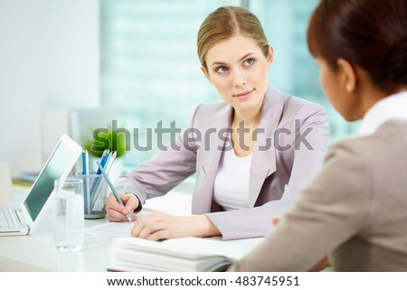 Serious businesswoman listening to woman and writing something