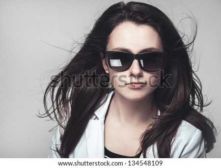serious businesswoman looking through glasses