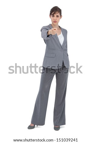 Serious businesswoman on white background pointing at camera - stock photo
