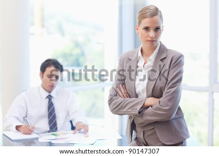 Serious businesswoman posing while her colleague is working in a meeting room - stock photo