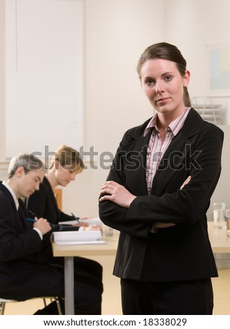 Serious businesswoman posing with co-workers meeting in conference room behind her - stock photo