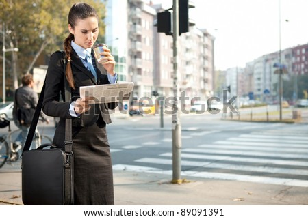 serious businesswoman reading newspaper, outdoor - stock photo