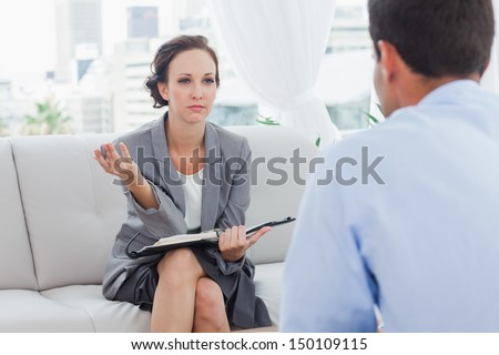 Serious businesswoman talking to her colleague in cosy bright office - stock photo