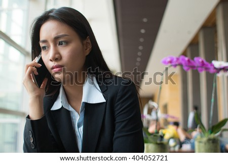 Serious businesswoman talking with her mobile phone in the hotel lobby.