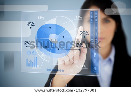 Serious businesswoman using blue pie chart interface  by touching it - stock photo