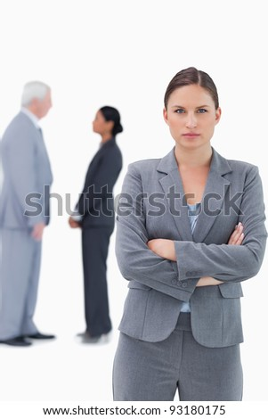 Serious businesswoman with arms folded and colleagues behind her against a white background - stock photo