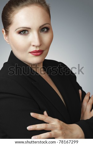 Serious businesswoman with crossed arms looking to camera - stock photo
