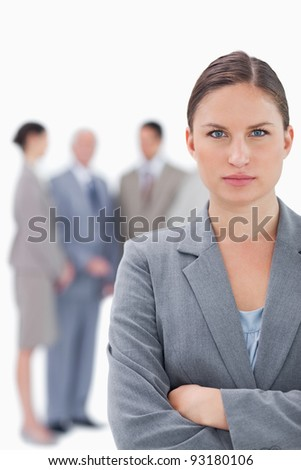 Serious businesswoman with her colleagues behind her against a white background - stock photo