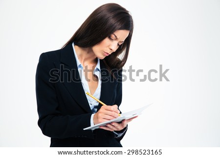 Serious businesswoman writing notes in notebook isolated on a white background - stock photo