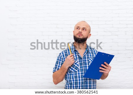 Serious Casual Bearded Business Man Holding Folder Think Look To Copy Space Pondering Doubtful Office Over White Brick Wall - stock photo
