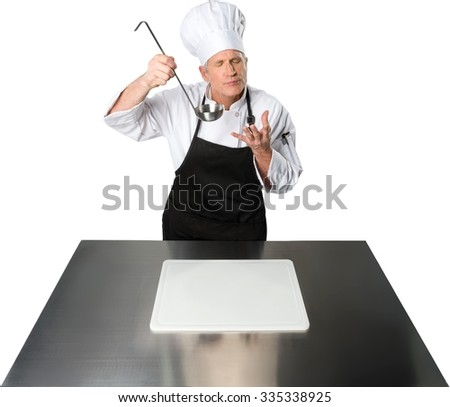 Serious Caucasian Chef  in uniform holding  a ladle with a cutting board in front - Isolated - stock photo