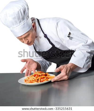 Serious Caucasian Chef scrutinizing a plateful of baked ziti - Isolated