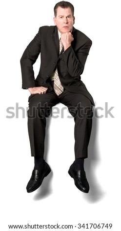 Serious Caucasian elderly man with short medium brown hair in business formal outfit with hands on thighs - Isolated