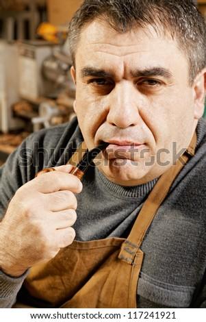 Serious caucasian guy smoking pipe in workshop - stock photo