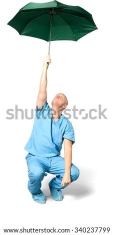 Serious Caucasian man in uniform using umbrella - Isolated - stock photo