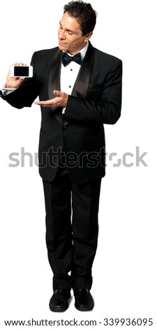 Serious Caucasian man with short black hair in evening outfit holding mobile phone - Isolated - stock photo