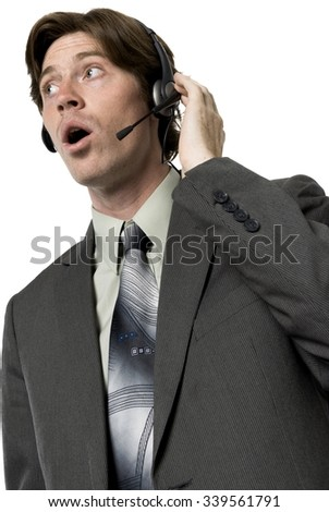 Serious Caucasian man with short dark brown hair in business formal outfit talking on headset - Isolated