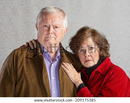 Serious Caucasian older couple over gray background - stock photo