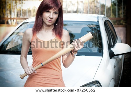 Serious caucasian redheaded woman standing by the car with a baseball bat - stock photo