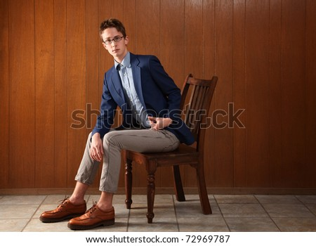 Serious Caucasian teen sitting on a wooden chair