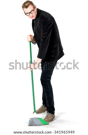 Serious Caucasian young man with short light blond hair in business formal outfit using broom - Isolated
