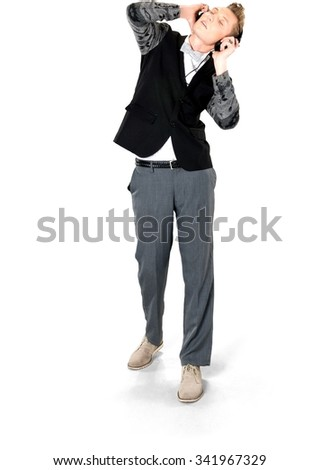 Serious Caucasian young man with short light blond hair in evening outfit using headphones - Isolated