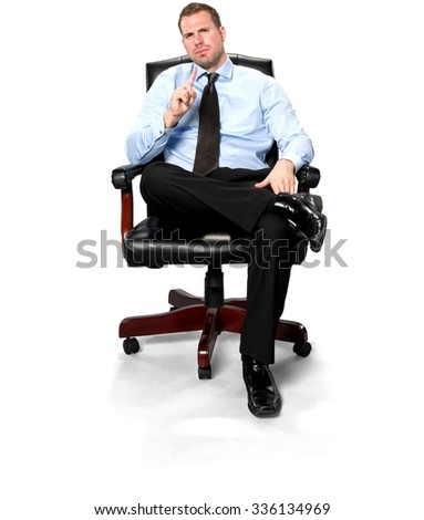Serious Caucasian young man with short medium brown hair in business formal outfit sitting in chair with hands in lap - Isolated