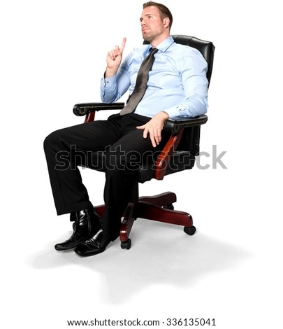 Serious Caucasian young man with short medium brown hair in business formal outfit sitting in chair with hands on thighs - Isola