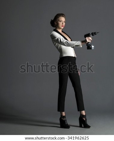 Serious Caucasian young woman medium brown in casual outfit holding power tool