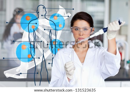 Serious chemist working with human dna interface in the lab - stock photo