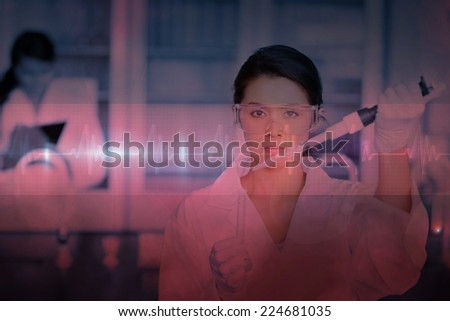 Serious chemist working with large pipette and test tube against ecg line in red and black - stock photo
