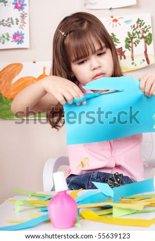 Serious child cutting paper by scissors. - stock photo