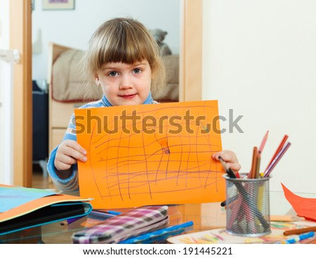 serious child with drawn paper in home interior