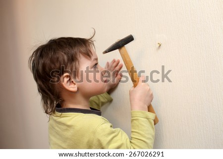 Serious child with hammer working at home - stock photo