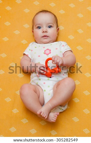 Serious chubby baby girl in bodysuit lying on her back on yellow orange sheet. Baby looking straight at the camera.  - stock photo