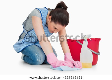 Serious cleaning woman wiping up the floor on the white background