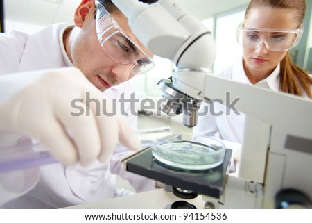 Serious clinician studying chemical element in laboratory with his assistant near by - stock photo