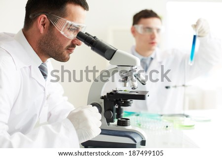 Serious clinicians studying chemical elements in laboratory - stock photo
