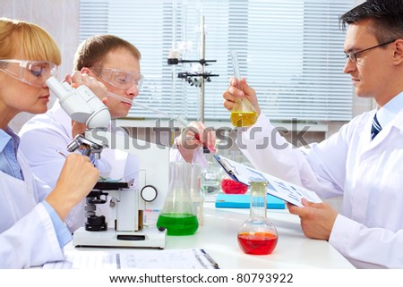 Serious clinicians studying new medicine in laboratory - stock photo