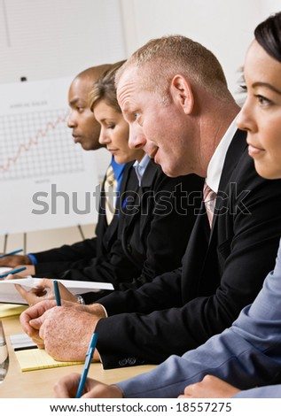 Serious co-workers listening during meeting in conference room - stock photo