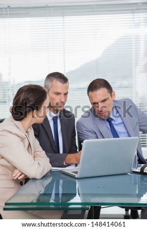 Serious colleagues working together on their laptop in bright office - stock photo