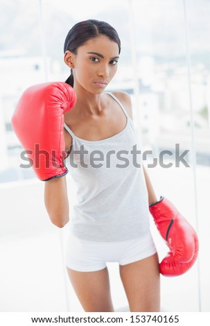 Serious competitive model with boxing gloves threatening camera in bright room at home