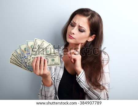 Serious concentrated thinking business lady thinking where invest money and how to earning more dollars - stock photo